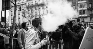 Un vapoteur fait démonstration de sa vape face caméra, à un journaliste présent sur le point de rassemblement.