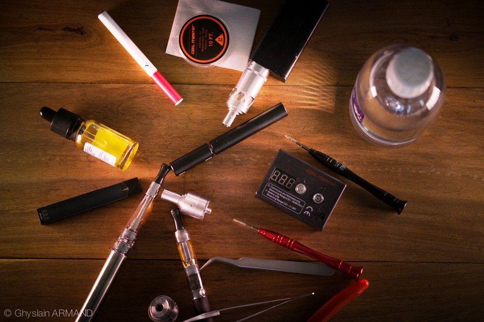 Différents modèles et pièces détachées de cigarette electronique posés sur une table