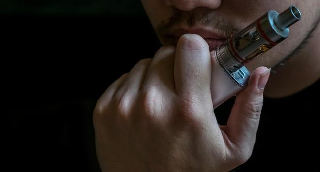 Homme tenant sa cigarette électronique