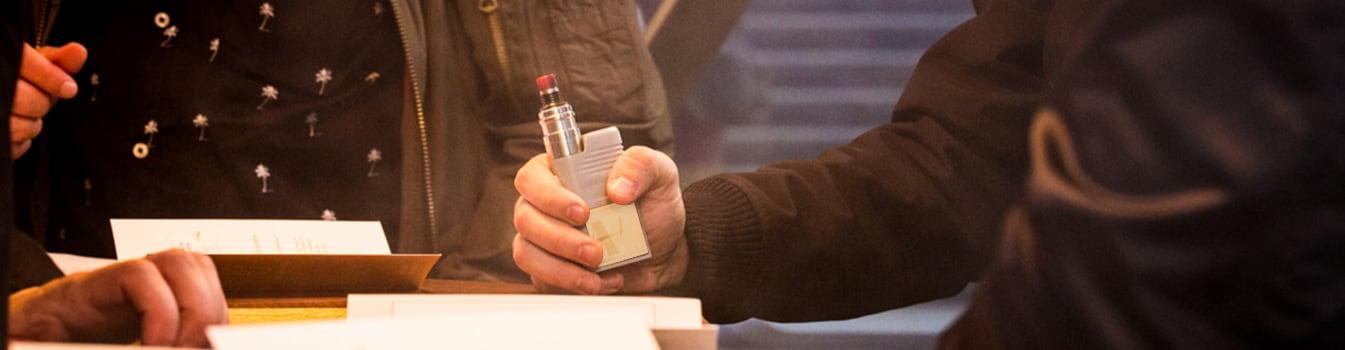 Un vapoteur qui tient dans sa main une cigarette électronique