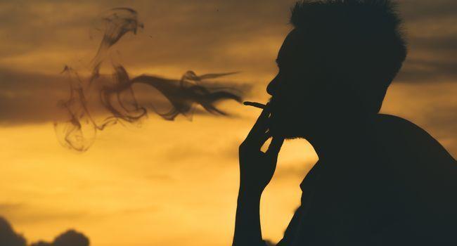 Homme fumant une cigarette sur un coucher de soleil