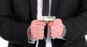 Homme avec des menottes qui tient des billets dans sa main